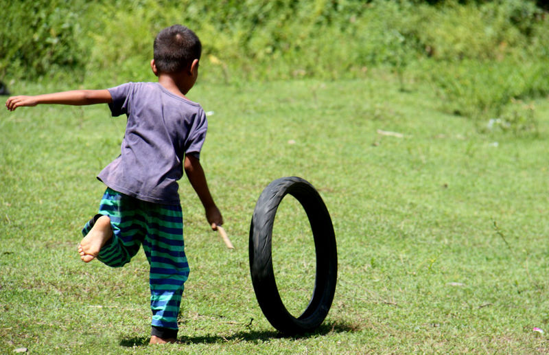 Rear View Of Boy Playing With Tire On Field