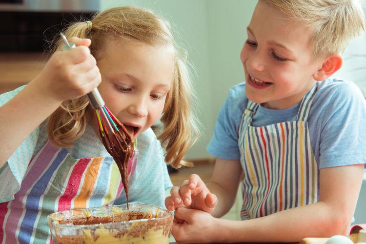 Siblings preparing food on table at home
