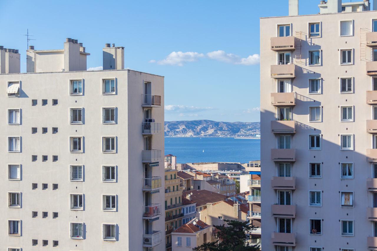 Residential Buildings By Sea Against Blue Sky