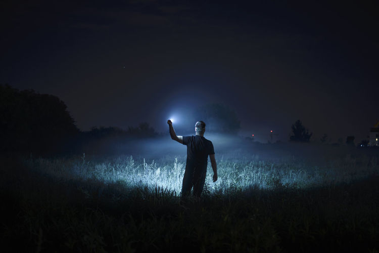 Rear view of man standing on field at night