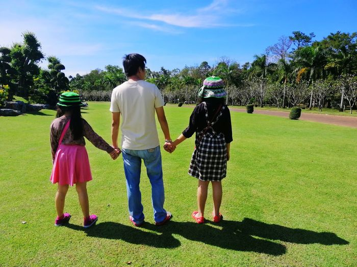 Family standing on lawn against blue sky