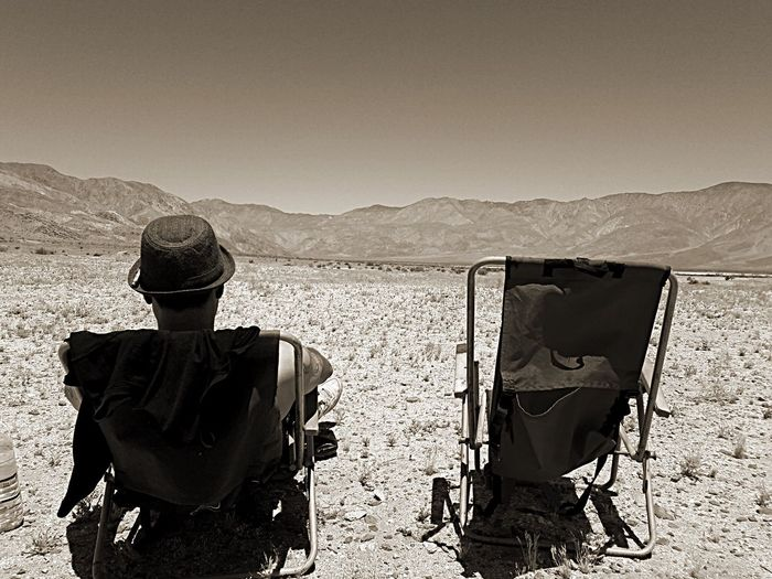 Rear view of man sitting in the desert