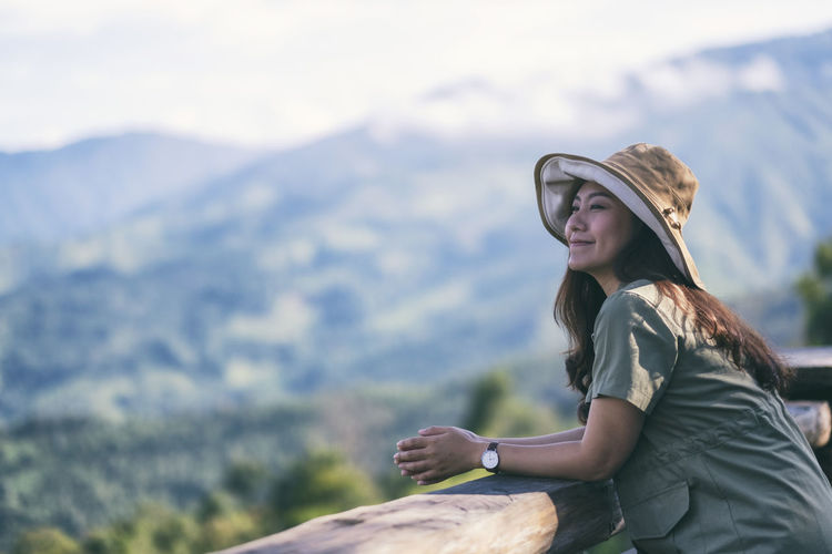 Woman wearing hat while standing by railing against mountain