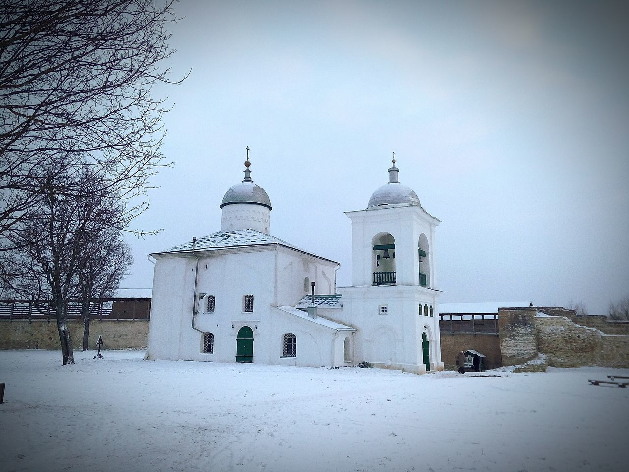 Low Angle View Of Izborsk Fortress By Snow Covered Field Against Sky