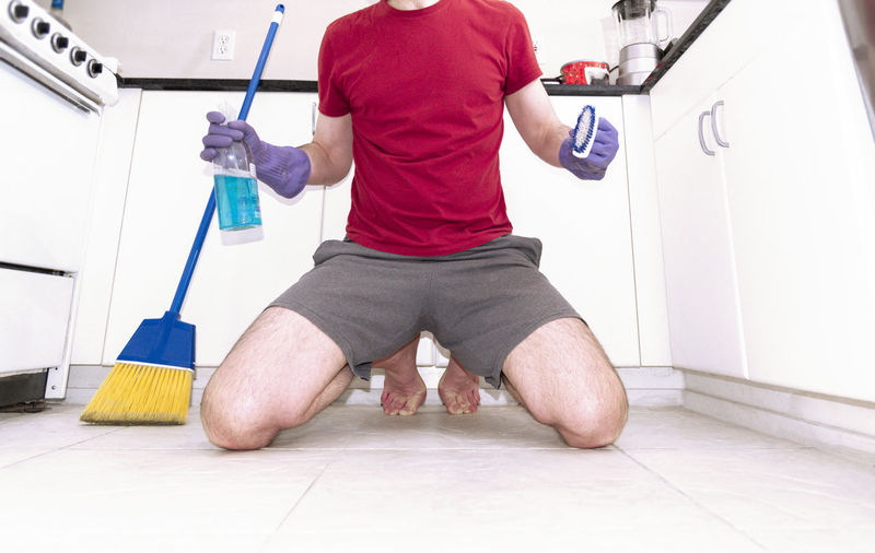 Rear view of man working on floor at home