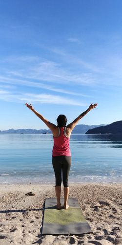 Rear view of woman with arms raised standing at beach against sky