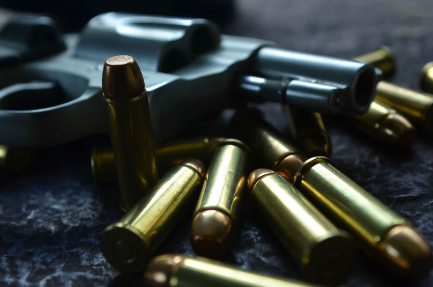 pistol and bullets Abundance Background Bullets Close-up Defocused Detail Focus On Foreground Gun Man Made Object Metal Metallic No People Part Of Pistol Selective Focus Still Life