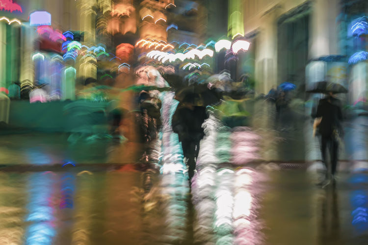 Abstract background of blurred people under umbrellas hurrying down the city street in rainy evening, impressionism style, colorful lighting. Intentional motion blur Illuminated City Night Motion City Rainy Rain Blurred Motion Blur Abstract Evening Street Bright People Reflection Lamps Pavement Umbrella Lifestyles Walking Group Of People Selective Focus Consumerism Shopping