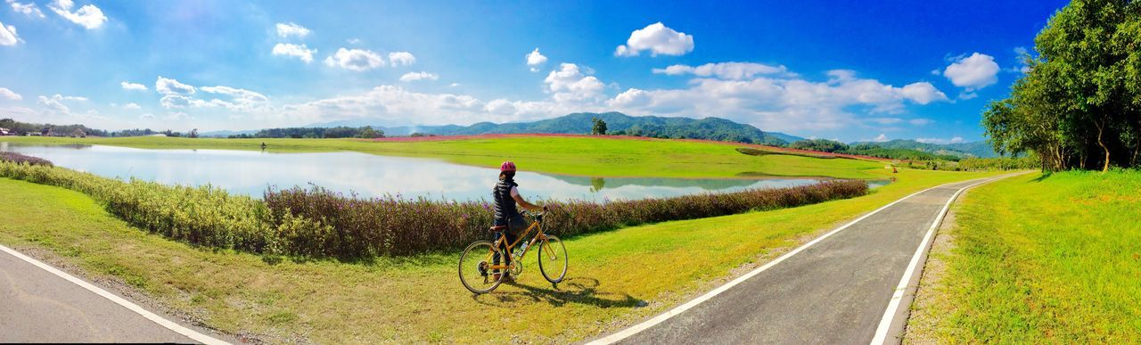 road, bicycle, transportation, tranquil scene, scenics, nature, non-urban scene, day, tranquility, landscape, beauty in nature, cycling, sky, outdoors, grass, the way forward, green color, no people, cloud - sky, tree, mountain, rural scene, water