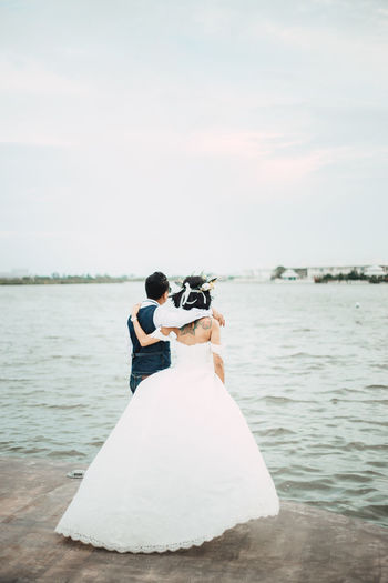 Adult Bride Bridegroom Celebration Couple - Relationship Event Life Events Love Men Nature Newlywed Positive Emotion Real People Rear View Sea Sky Two People Water Wedding Women