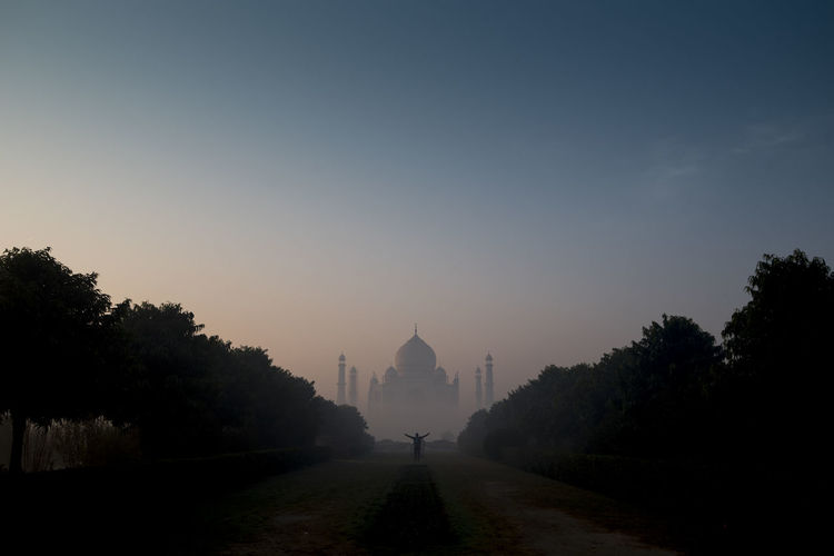 Full length of man standing against taj mahal during sunrise