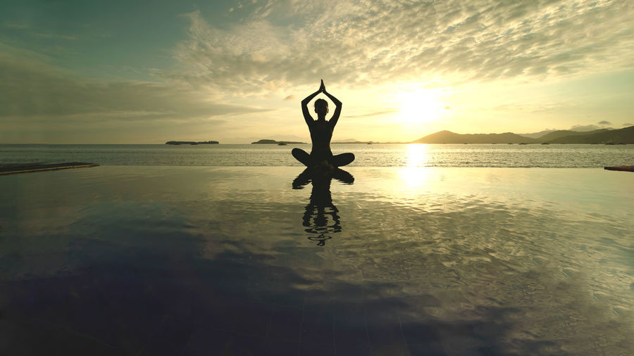 Silhouette woman doing yoga at beach during sunset