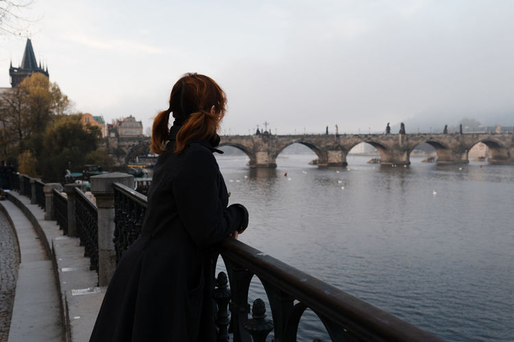 Side view of woman standing on bridge over river