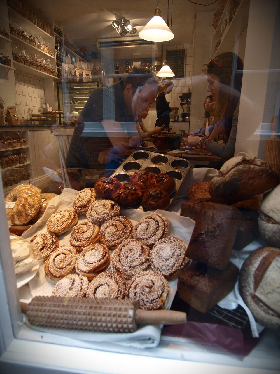 food and drink, bakery, freshness, food, baked, sweet food, indoors, store, retail, display cabinet, real people, dessert, for sale, bread, indulgence, small business, variation, men, temptation, day, ready-to-eat, loaf of bread, one person, people