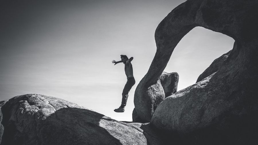 Low angle view of man jumping over boulder against sky