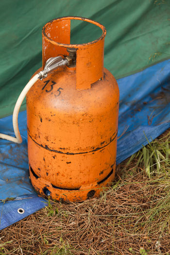 Orange gas cylinder on land