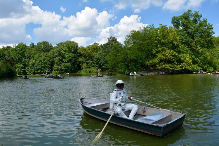 Spacesuit sitting in boat on river against sky