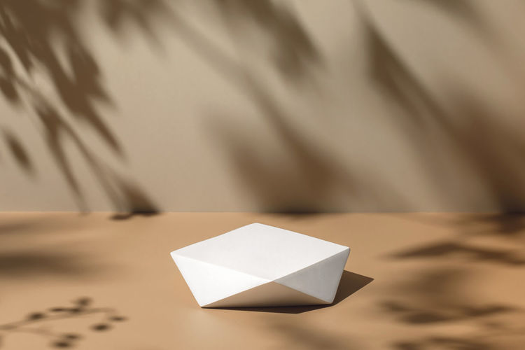 High angle view of paper on table against white wall