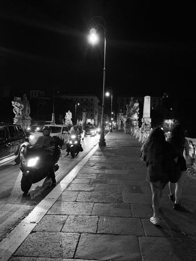 People on illuminated street at night