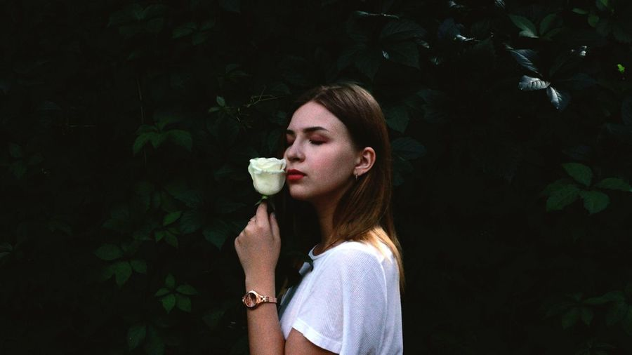 Side view of young woman holding rose