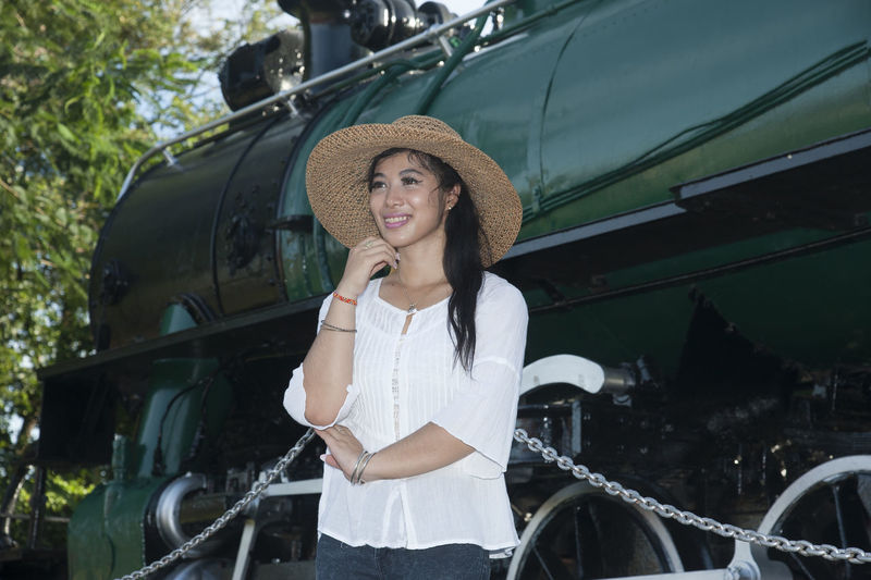 Pretty Asian Women standing and posing at Steam locomotive. Ancient Asian  Hat Show Steam Thailand Beautiful Woman Day Female Front View Leisure Activity Lifestyles Locomotive Mode Of Transport Old One Person Outdoors Portrait Posing Real People Smiling Standing Transportation Young Adult Young Women