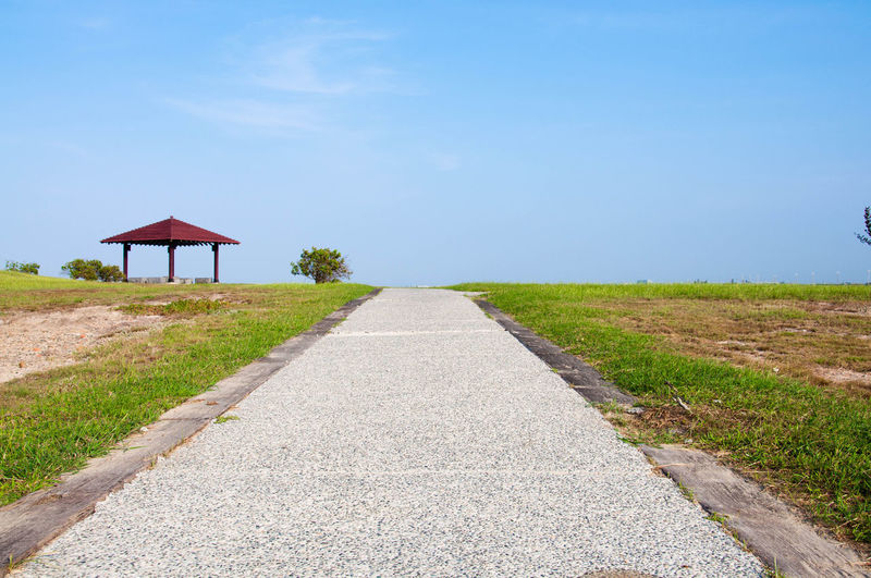 Footpath by road against sky