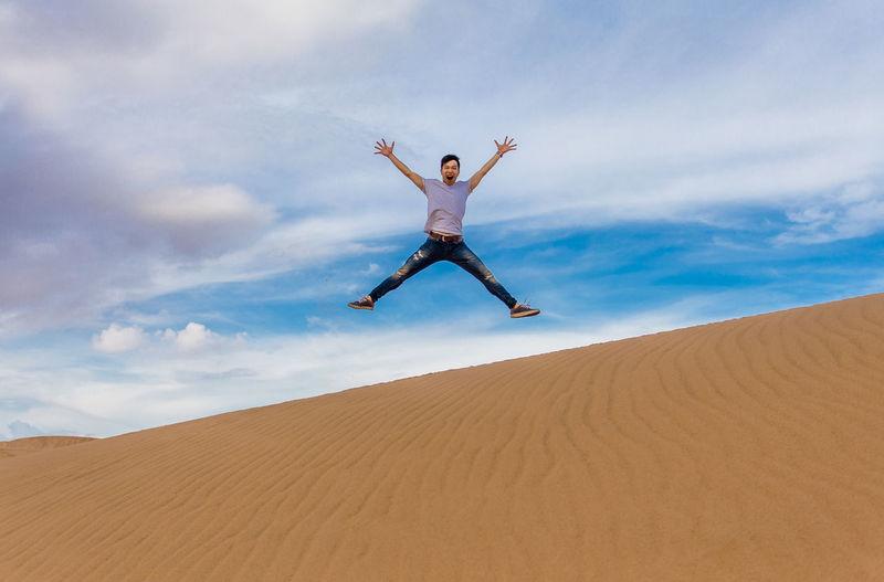 Man jumping over desert against sky