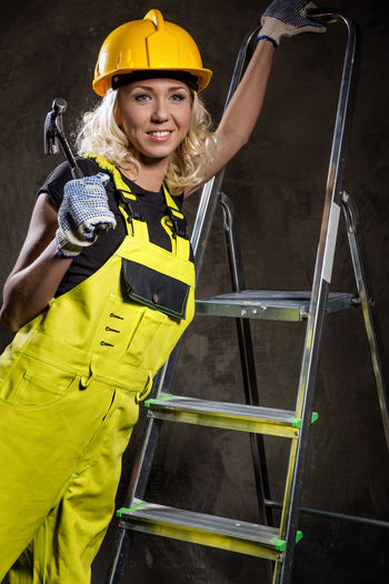 Female worker looking away while climbing ladder against wall