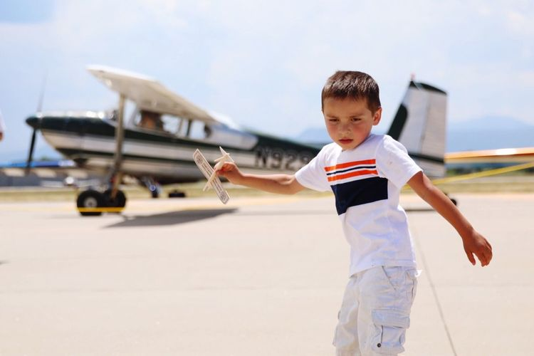 Cute Boy With Toy Airplane At Runway During Sunny Day