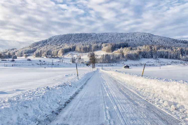 Snow covered road by snowcapped mountain against sky