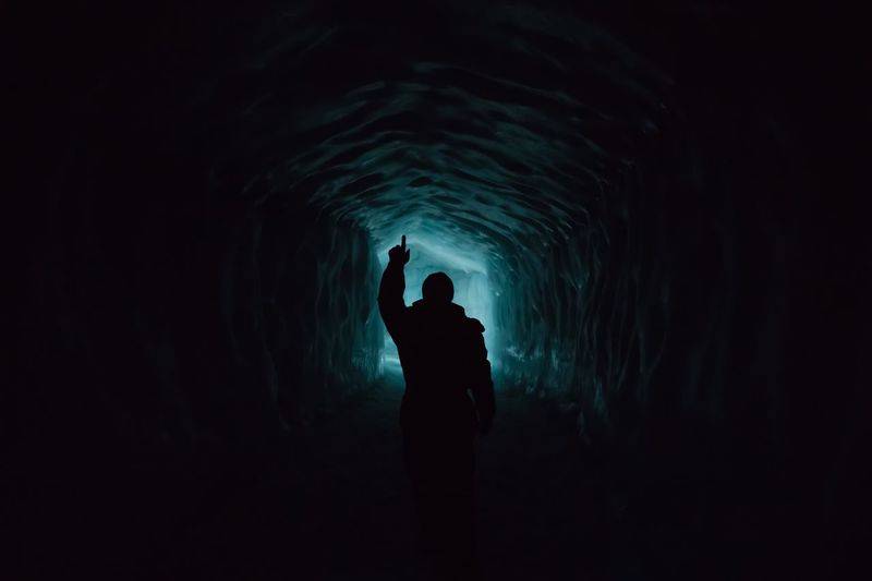 Silhouette man standing in tunnel