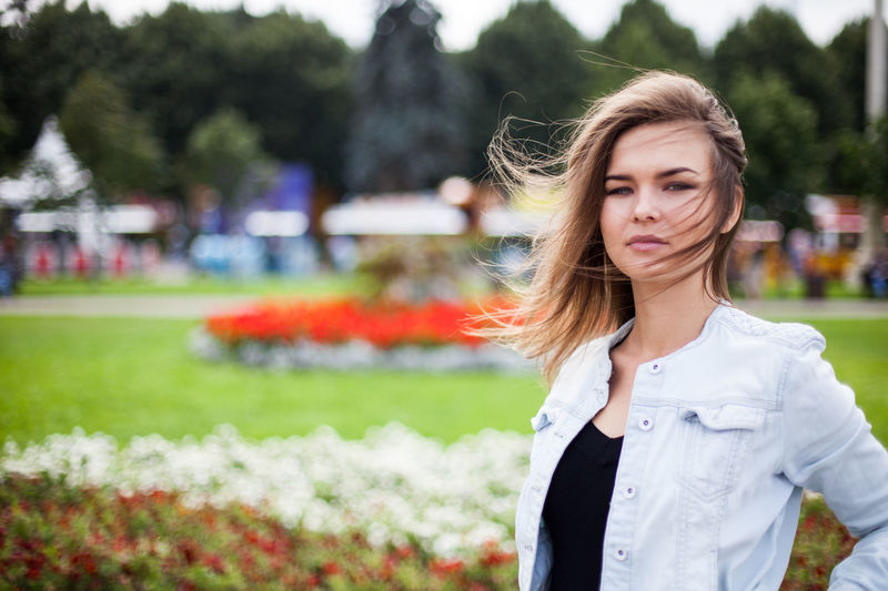 Beautiful young woman standing against trees in park
