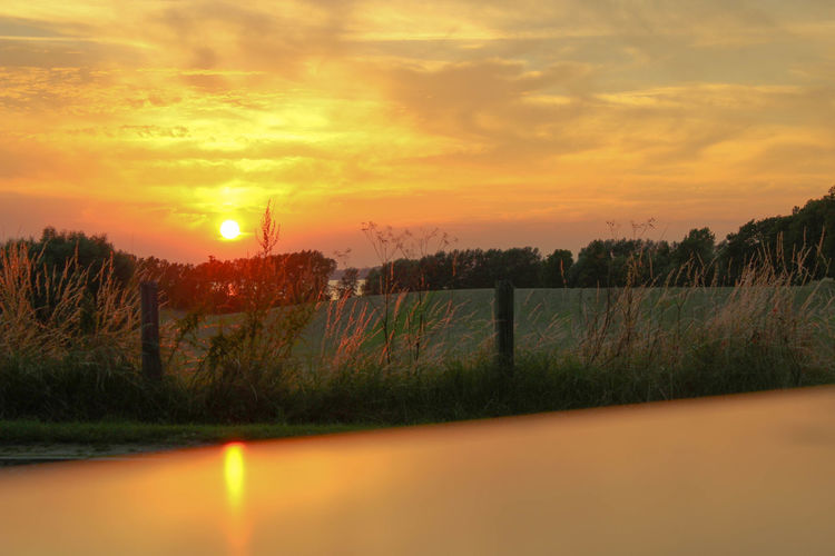 Fence by canal against sky during sunset