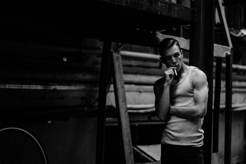 Man looking away while holding cigarette