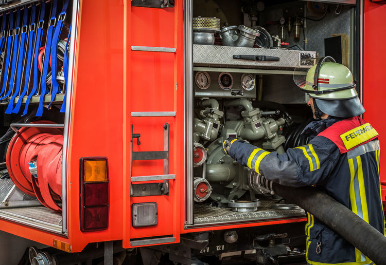 Firefighter attaching hose to machinery