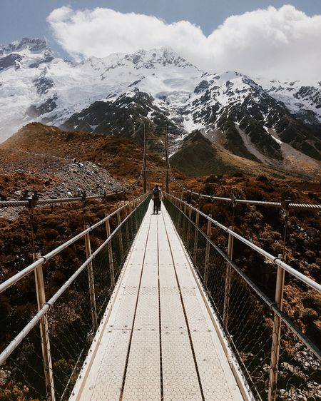 Young man standing on footbridge against snowcapped mountain