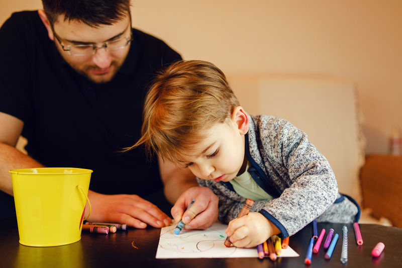 Father and son coloring on table at home
