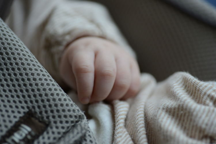 Cropped image of baby on fabric
