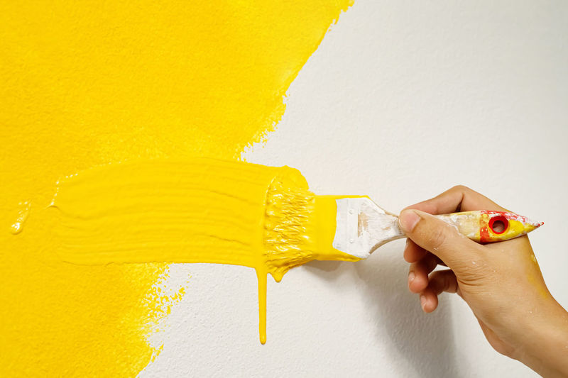 Low angle view of woman hand against yellow wall
