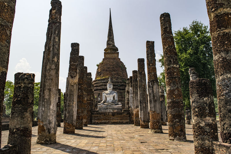 Ruined pagoda and buddha statue on field against clear blue sky