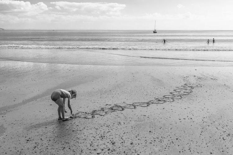 Girl making design on wet sand at beach against sky
