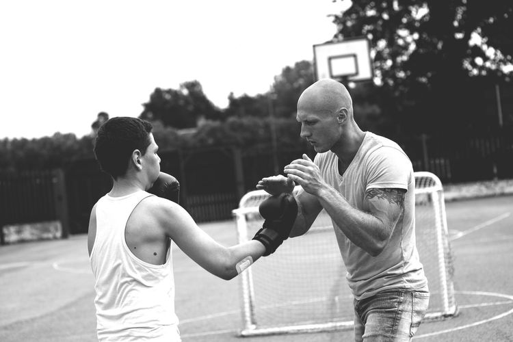 Young Male Trainer Teaching Boxing To Boy