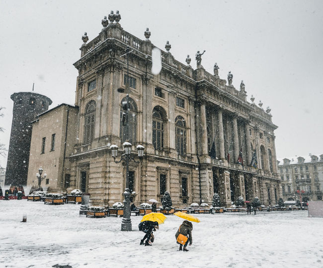Architecture Building Exterior Built Structure Clear Sky Cold Temperature Day Frozen History Large Group Of People Leisure Activity Lifestyles Men Nature Outdoors Real People Sky Snow Snowing Travel Destinations Vacations Walking Warm Clothing Weather Winter Winter Sport