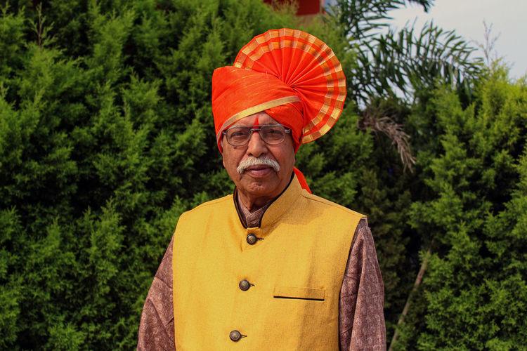 Portrait of senior man in turban standing against trees