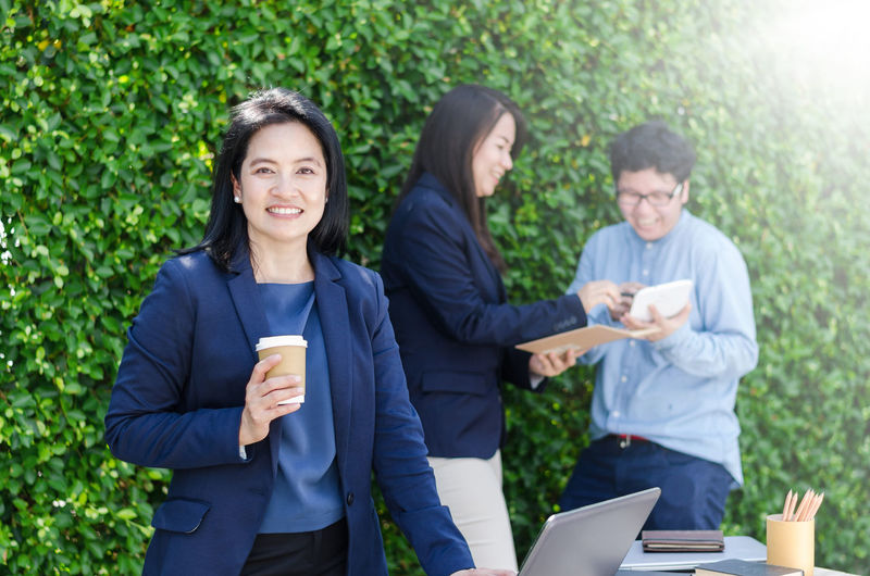 Portrait Of Smiling Businesswoman With Coffee Against Colleagues Discussing At Cafe