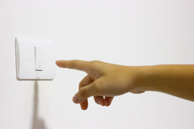 Close-up of person reaching to button on wall