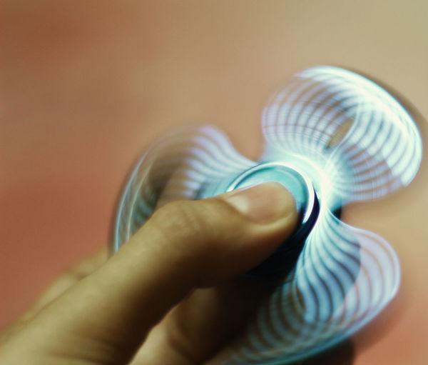 Close-up of hands holding fidget spinner
