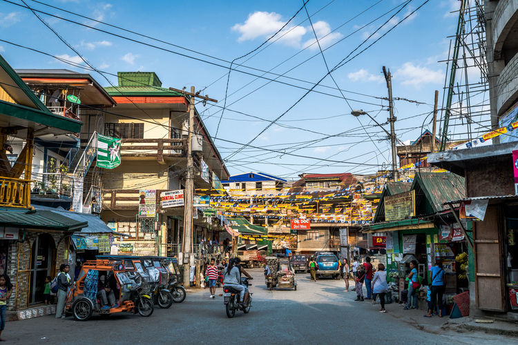 Architecture Building Exterior Built Structure Transportation City Street Mode Of Transportation Sky Group Of People Market Real People Land Vehicle Day Cable Men Incidental People Nature Women Market Stall Building Outdoors Electricity  Street Market