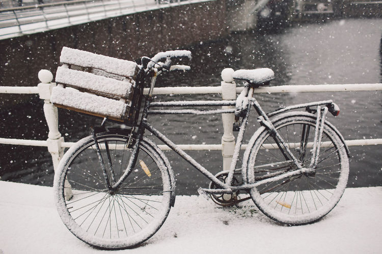 Snow covered bicycle parked on bridge over canal