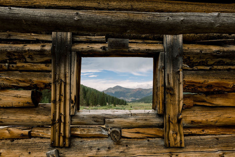 Wooden log cabin against sky